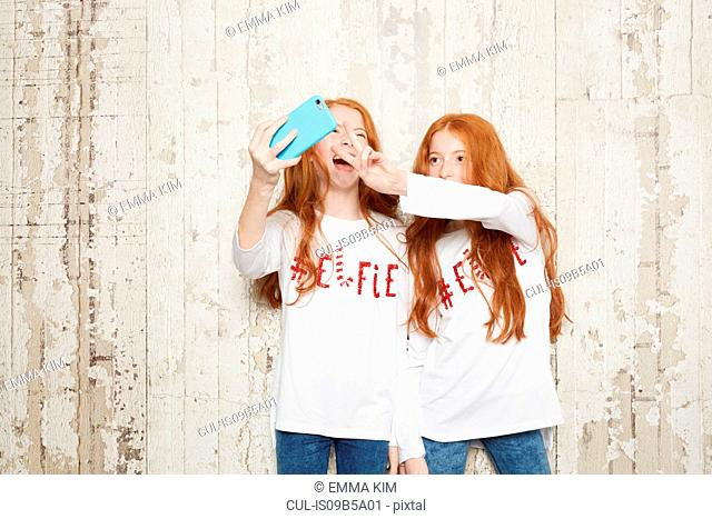 Portrait of twin sisters wearing Christmas jumpers, taking selfie using smartphone
