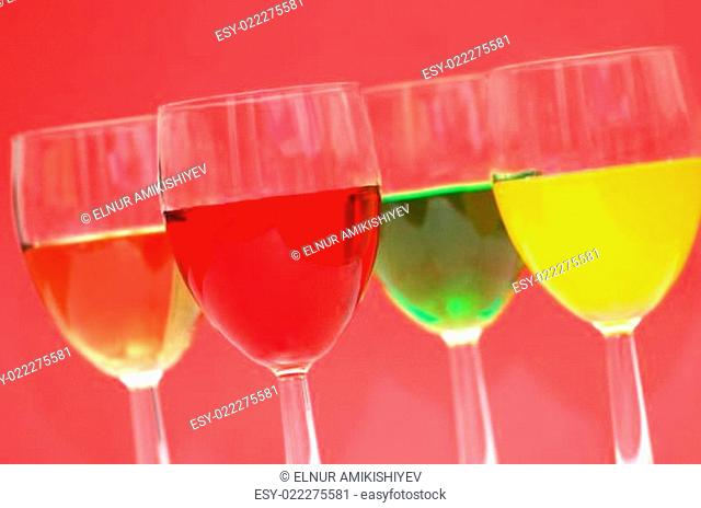 Glasses with drinks of various colours on red background