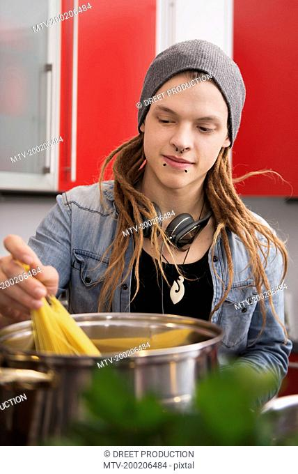 Young man cooking spaghetti in the kitchen, Munich, Bavaria, Germany