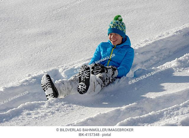 Boy on a minibob in deep snow, Bad Heilbrunn, Upper Bavaria, Bavaria, Germany