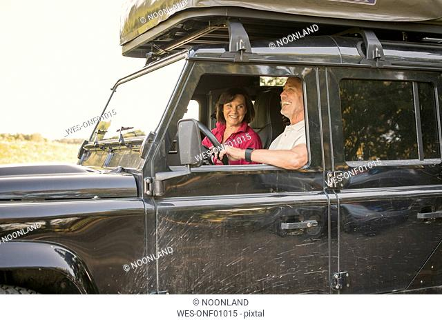 Happy senior couple on a trip in a cross country vehicle