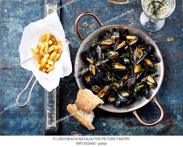 Mussels in copper cooking dish and french fries on blue background