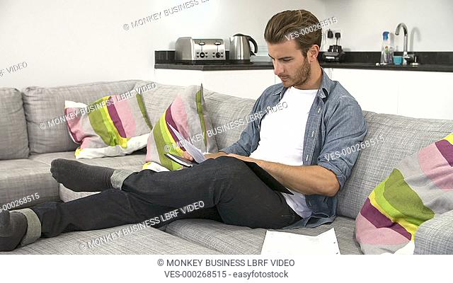 Young man at home looking at bills and using digital tablet to check personal finances.Shot on Sony FS700 in PAL format at a frame rate of 25fps