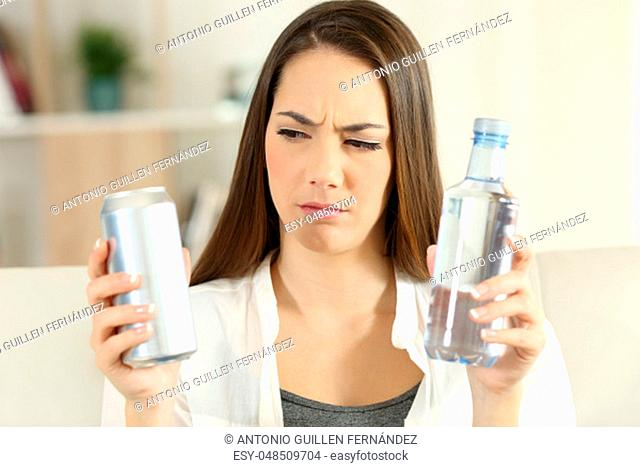 Front view portrait of a confused girl deciding between soda refreshment and water bottle at home