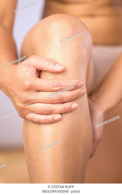 Germany, Freiburg, Mid adult woman holding her knee, close up