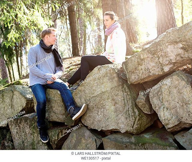 Young couple in nature resting on big rocks in woods during a trek