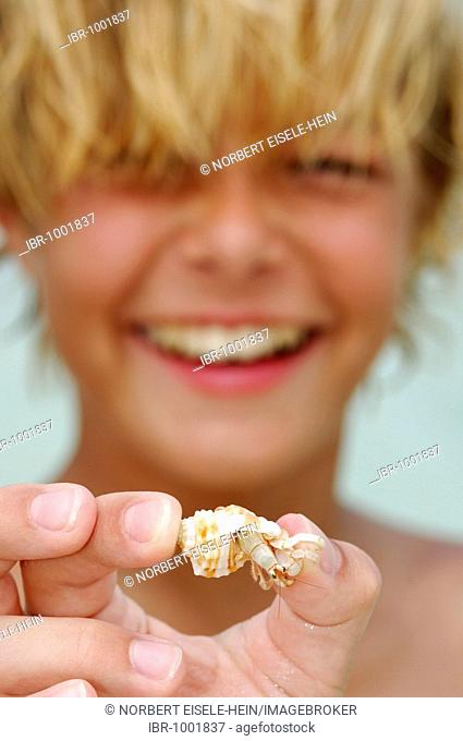 Young boy with a hermit crab, laughing, Baros Resort, The Maldives, Indian Ocean