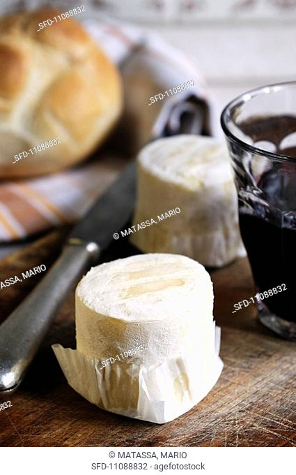 An arrangement of goat's cheese, a glass of red wine and bread