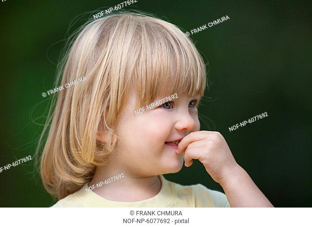 Outdoor portrait of a little boy with long blond hair