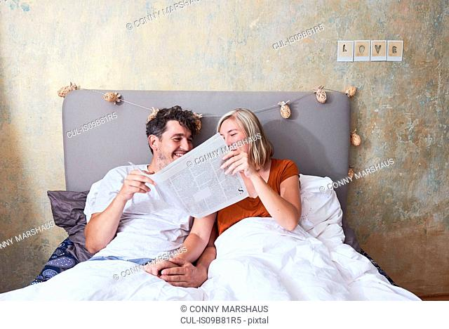 Couple in bed, holding hands, sharing newspaper