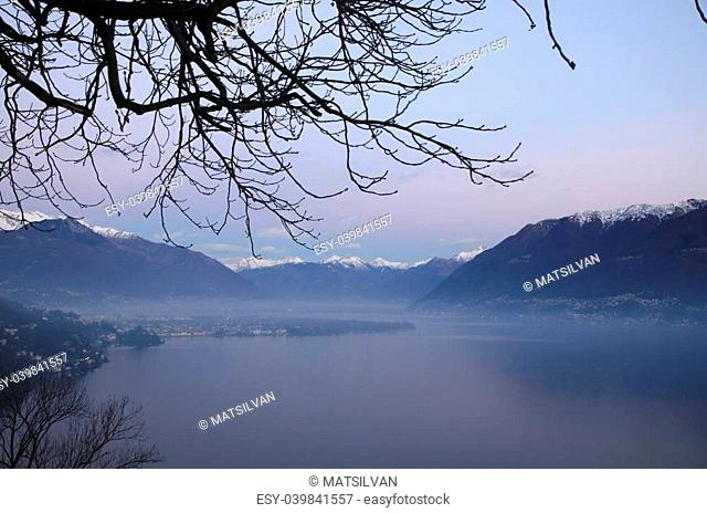 Alpine lake with fog in blue hour with island and snow-capped mountain