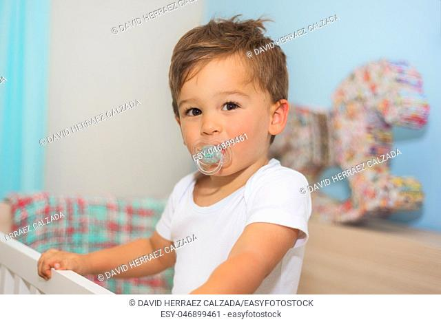Adorable little boy in the crib with pacifier
