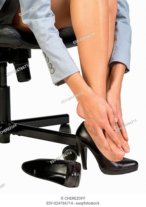 Closeup of tired businesswoman sitting on chair and massaging her feet. Isolated over white background