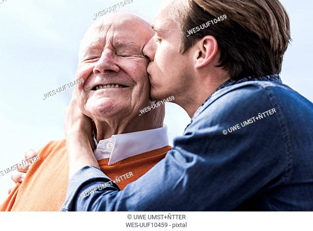 Adult grandson kissing senior man outdoors