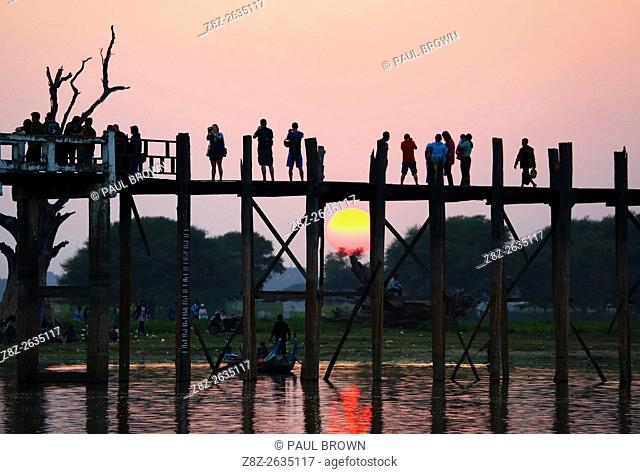 People crossing the U Bein Bridge across the Taungthaman Lake at sunset in Amarapura, Mandalay, Myanmar (Burma) believed to be the oldest and longest teakwood...