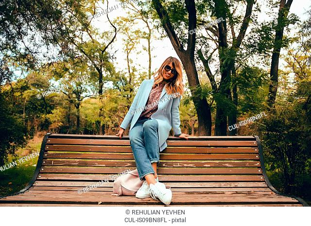 Stylish woman with long blond hair sitting on park bench, full length portrait