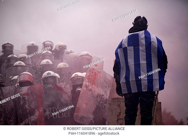 Greek man with Greek flag after tear gas in front of Parliament, during protest against recognition FYROM as North Macedonia. 20.01