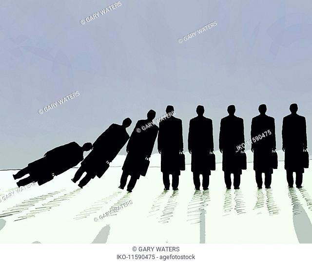 Row of businessmen falling in domino effect