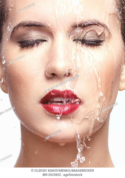 Water running over woman's face with red lipstick