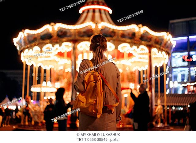 Young woman by carousel at night