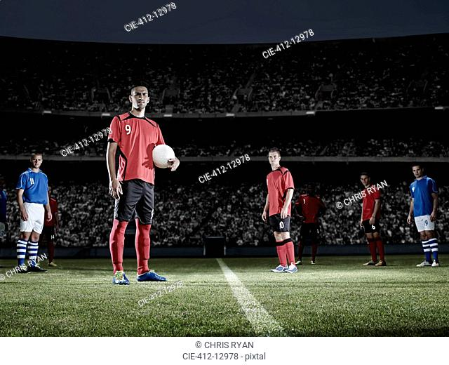 Soccer player holding ball on field