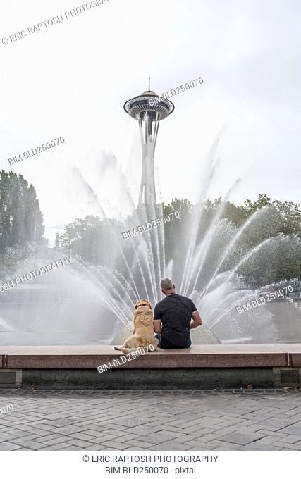 Caucasian man and dog sitting on fountain near tower