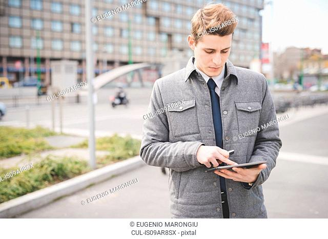 Portrait of young businessman commuter using digital tablet