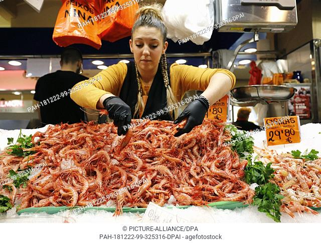 dpatop - 22 December 2018, Spain, Palma de Mallorca: Marta offers her customers shrimps in the Olivar market hall. Dishes with prawns
