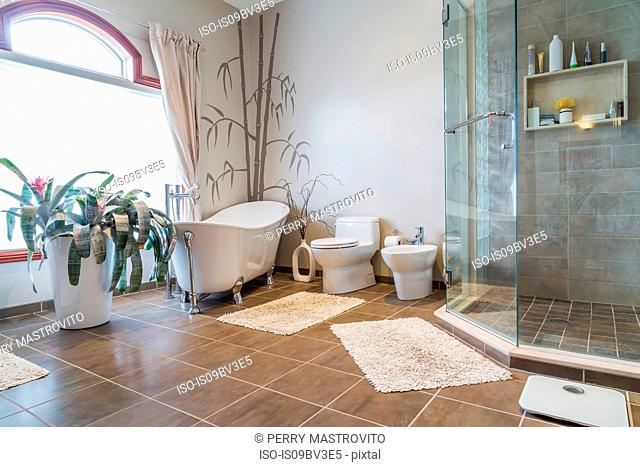 Free standing bathtub, bidet, clear glass shower stall in ensuite, grey nuanced ceramic tile floor