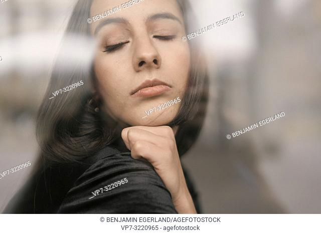 portrait of a woman with closed eyes, defiant emotion, in Munich, Germany