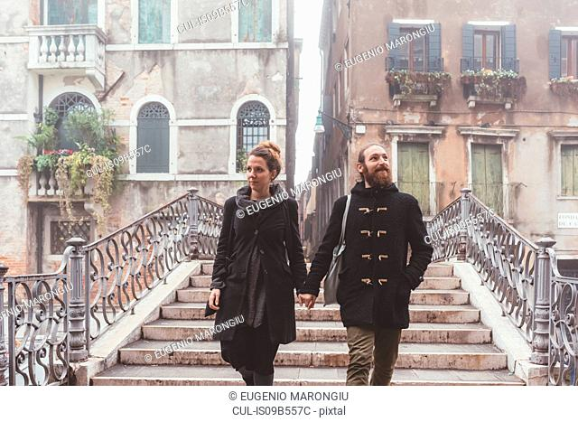 Couple holding hands and moving down stairway, Venice, Italy
