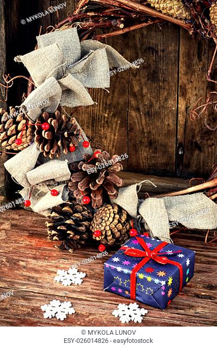 gift box on the background of a wicker wreath decorated for Christmas with pine cones and berries