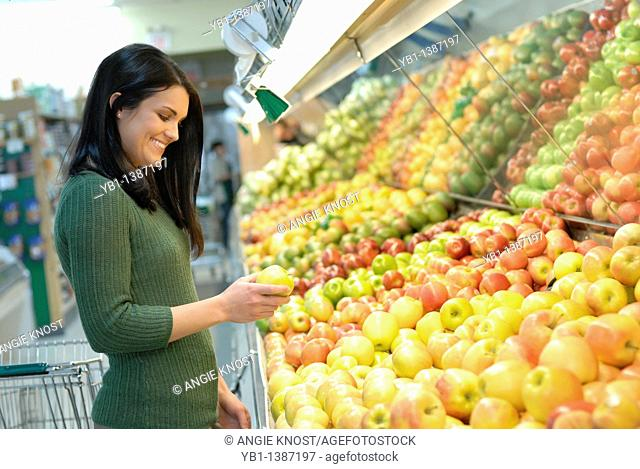 Attractive woman grocery shopping, in the produce section