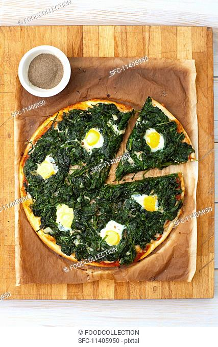 Pizza fiorentina with spinach and quail eggs, sliced