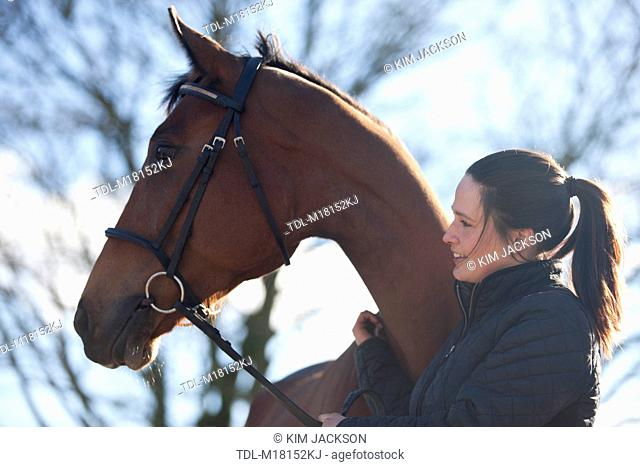 A young standing with a Thoroughbred horse, side view