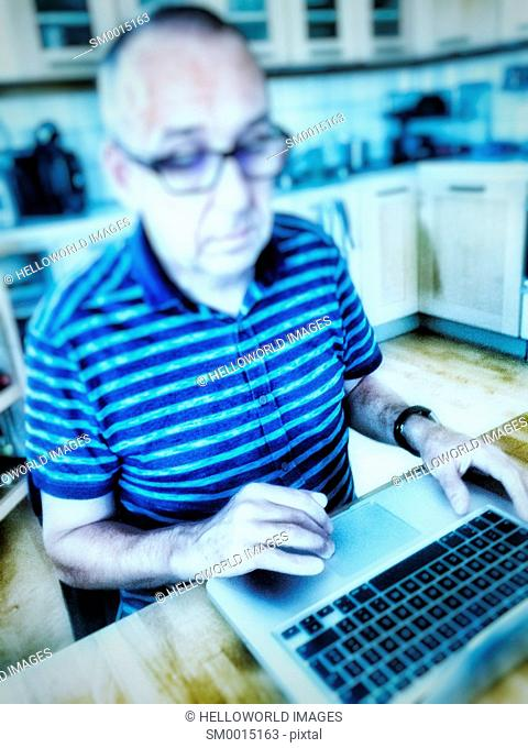 Serious middle aged man in striped T shirt working on laptop at kitchen table, Stockholm, Sweden