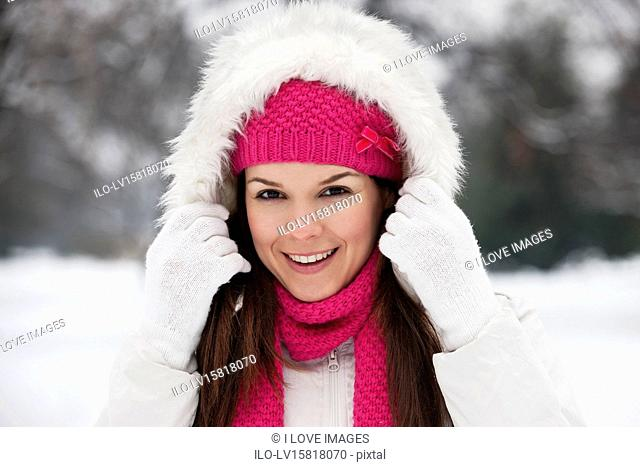 A young woman putting up the hood of her coat, smiling
