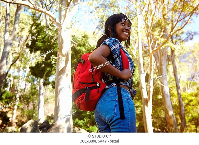 Young woman hiking through forest, looking over shoulder, smiling, Cape Town, South Africa