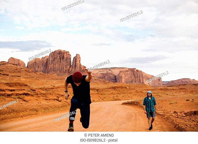 Two men, one sprinting and one walking along dirt track, Monument Valley, Arizona, USA