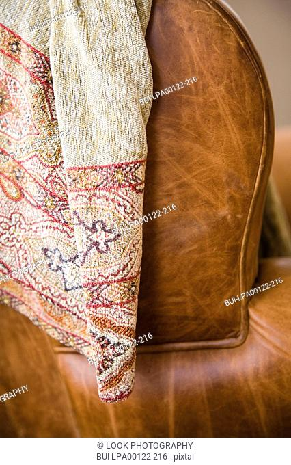 Detail of leather couch arm with throw blanket