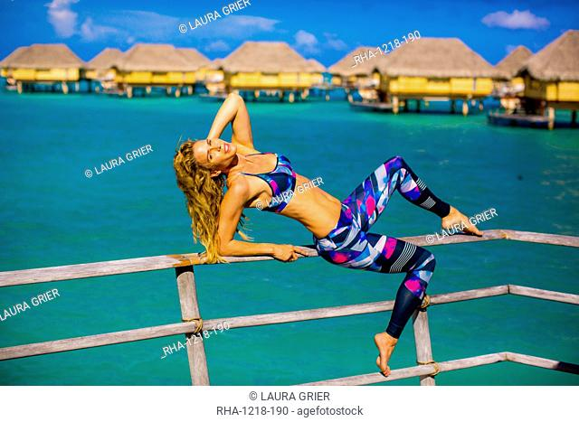 Woman lounging in front of overwater bungalows, Le Taha'a Resort, Tahiti, French Polynesia, South Pacific, Pacific