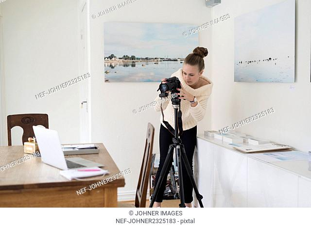 Woman photographing laptop at home