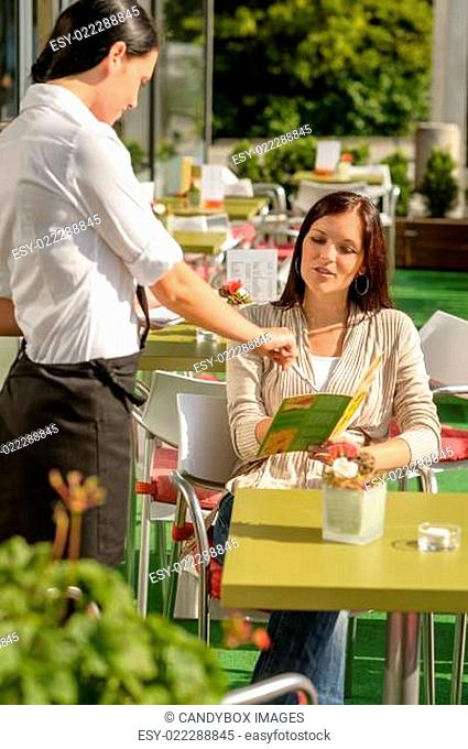 Waitress pointing menu woman in cafe bar
