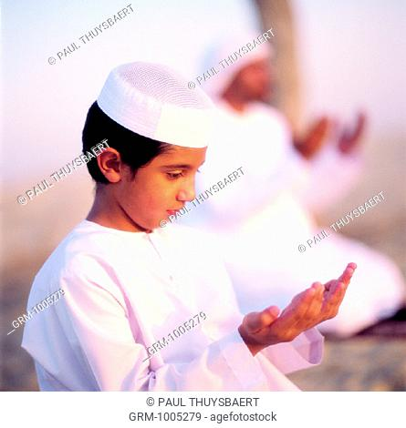 Arab father and son during prayer (Dou'aa)