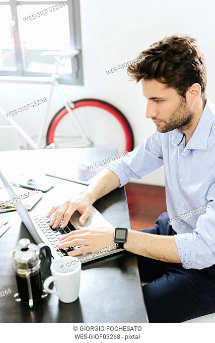 Young businessman working in office, using laptop