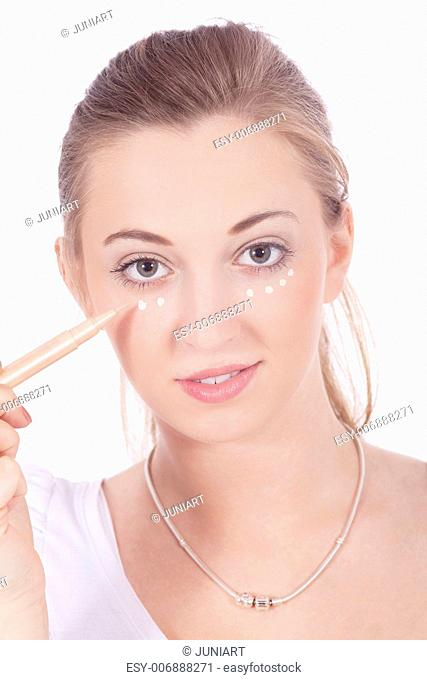 young beautiful woman applying concealer on face isolated