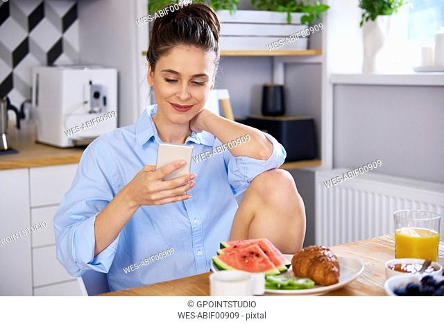 Young woman at home in kitchen, using smartphone
