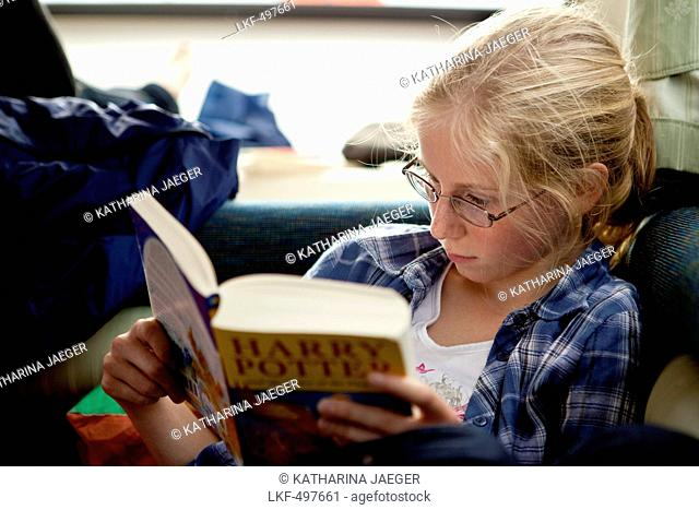 Young girl reading Harry Potter book intensely, Athlone, County Offaly, Ireland, Europe