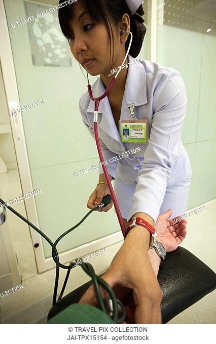 Thailand, Bangkok, Nurse Taking Patients Blood Pressure
