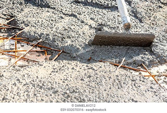 Spreading ready mix concrete on construction site